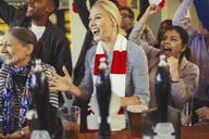 Enthusiastic sports fans cheering and watching game at bar - CAIF05595