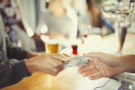 Woman paying bartender with credit card at bar - CAIF05601