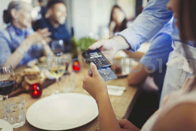 Woman with credit card paying waiter, using credit card reader at restaurant table - CAIF05619