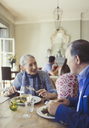 Senior couple talking and dining at restaurant table - CAIF05637