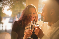 Smiling, romantic couple toasting champagne glasses in restaurant - CAIF05649
