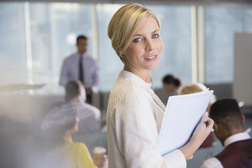 Portrait smiling businesswoman with paperwork in conference room meeting - CAIF05673