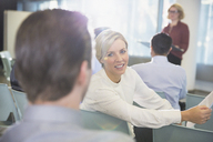 Smiling businesswoman talking to businessman in conference audience - CAIF05697