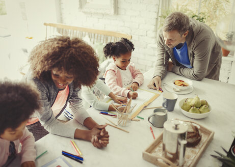 Multi-ethnic young family coloring with markers at table - CAIF05709