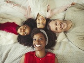 Overhead portrait smiling multi-ethnic young family laying on bed - CAIF05715