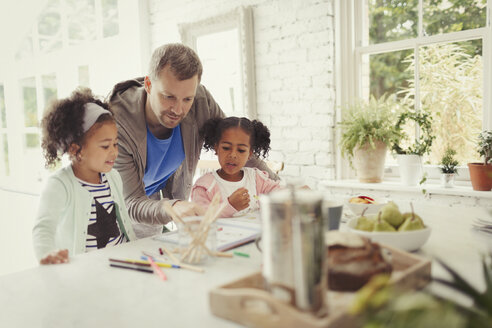 Multi-ethnic father and daughters coloring in kitchen - CAIF05724