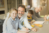 Portrait male gay parents helping children with homework at kitchen counter - CAIF05733