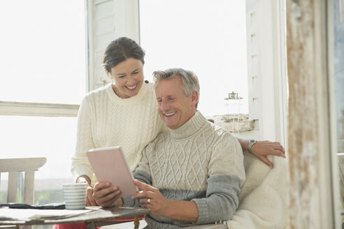 Smiling mature couple using digital tablet at table on sunny sun porch - CAIF05751
