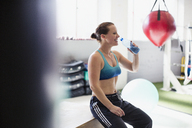 Female boxer drinking water and resting post workout in gym - CAIF05805