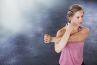 Young woman stretching arm and shoulder in gym - CAIF05814