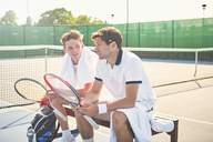 Young male tennis players resting with tennis rackets on sunny tennis court - CAIF05826