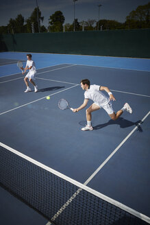 Young male tennis doubles players playing tennis, reaching for the ball on sunny blue tennis court - CAIF05832