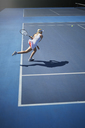 Young female tennis player playing tennis, swinging tennis racket on sunny blue tennis court - CAIF05835