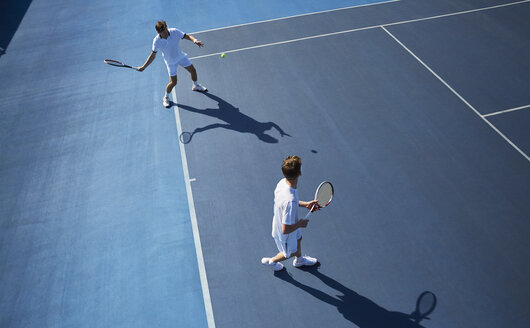 Young male doubles tennis players playing tennis on sunny blue tennis court - CAIF05841