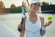 Portrait smiling, confident young female tennis player holding tennis racket and tennis ball on tennis court - CAIF05865