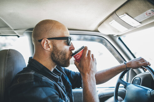 Young man with sunglasses and beard on a road trip with takeaway drink - GUSF00408