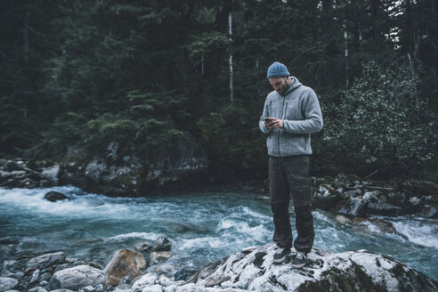 Canada, British Columbia, Glacier National Park, man with cell phone at Illecillewaet River in forest - GUSF00435
