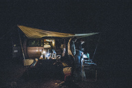 Canada, British Columbia, two men cooking under tarp at minivan at night - GUSF00438