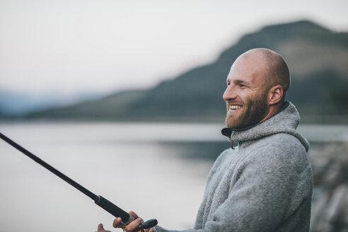 Canada, British Columbia, happy man fishing at Kinbasket Lake - GUSF00453