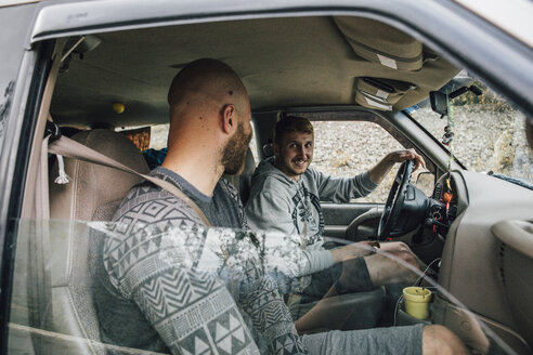 Two smiling young men in car on a road trip - GUSF00486