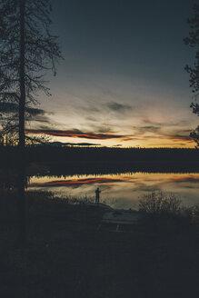 Canada, British Columbia, man fishing at Duhu Lake at sunset - GUSF00489