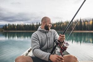Canada, British Columbia, man fishing in canoe on Boya Lake - GUSF00501