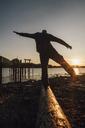 Canada, British Columbia, Port Edward, man balancing on log at sunset - GUSF00516