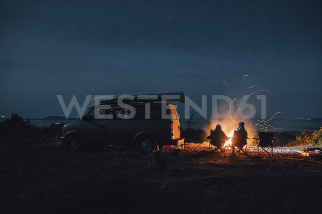 Canada, British Columbia, Prince Rupert, two men sitting at camp fire at minivan at night - GUSF00519