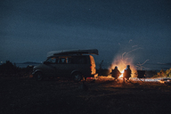 Canada, British Columbia, Prince Rupert, two men sitting at camp fire at minivan at night - GUSF00519