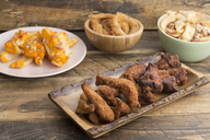 Typical american food, potatoes with cheese and bacon, fried onion rings and chicken wings - SKCF00343