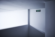 Neon exit sign on white wall - CAIF05922