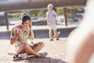 Smiling teenage girl listening to headphones on skateboard in sunny skate park - CAIF05928
