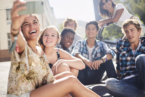 Smiling teenage friends posing for selfie on sunny urban street - CAIF05931