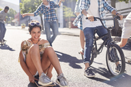 Enthusiastic teenage girl skateboarding with friends on sunny urban street - CAIF05937