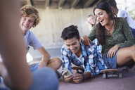 Teenage friends hanging out texting with cell phone at skate park - CAIF05940