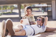 Teenage couple hanging out using digital tablet - CAIF05946
