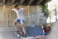 Teenage boy doing skateboard stunt at skate park - CAIF05967