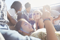 Teenage friends hanging out texting on sunny day - CAIF05970