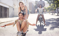 Teenage girls riding skateboard and BMX bicycle on sunny urban street - CAIF05979