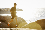 Male triathlete running on rocky trail along sunny ocean - CAIF05991
