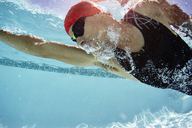 Male swimmer swimming underwater in swimming pool - CAIF06006