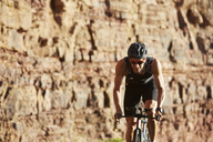 Male triathlete cyclist cycling along sunny rocks - CAIF06009