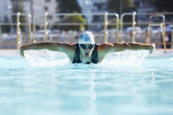 Male swimmer athlete doing butterfly stroke swimming in swimming pool - CAIF06012