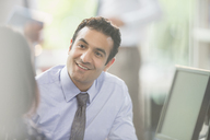 Attentive, smiling businessman listening to colleague in meeting - CAIF06033