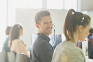Portrait smiling male telemarketer wearing headset at computer in sunny office - CAIF06042