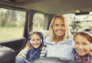 Portrait smiling mother and daughters wearing headphones in back seat of car - CAIF06054
