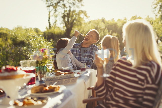 Playful daughter feeding father at sunny garden party patio table - CAIF06057