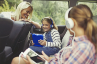 Mother watching daughters with headphones using digital tablets in back seat of car - CAIF06063