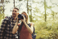 Couple hiking and photographing woods with digital SLR camera - CAIF06066