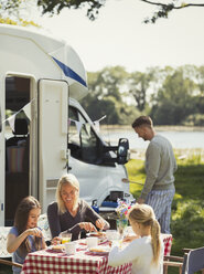 Family enjoying breakfast at table outside sunny motor home - CAIF06072